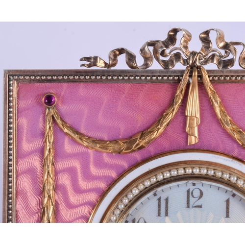 963 - AN UNUSUAL CONTINENTAL SILVER GILT GEM SET PINK ENAMEL DESK CLOCK modelled with a seed pearl banded ...