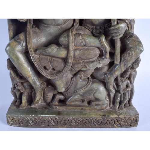 436 - A LARGE 19TH CENTURY INDIAN HARDSTONE FIGURE OF SHIVA AND PARVATI modelled seated upon Nandi. 38 cm ...