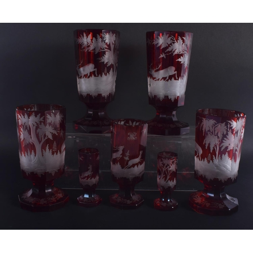 35 - SEVEN ANTIQUE BOHEMIAN RUBY GLASS GOBLET BEAKERS decorated with deer. Largest 18.5 cm high. (7)
