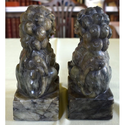 14 - A PAIR OF 19TH CENTURY CHINESE CARVED SOAPSTONE BUDDHISTIC LIONS modelled upon square bases. 18 cm x...