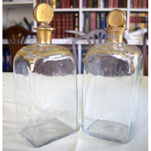 23 - A PAIR OF ANTIQUE BOHEMIAN CLEAR AND GILDED STRAIGHT SIDED GLASS DECANTERS modelled in the neo class...
