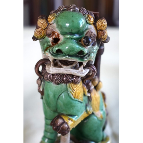 28 - A PAIR OF 17TH CENTURY CHINESE EGG AND SPINACH GLAZED BUDDHISTIC LIONS modelled upon similarly decor...