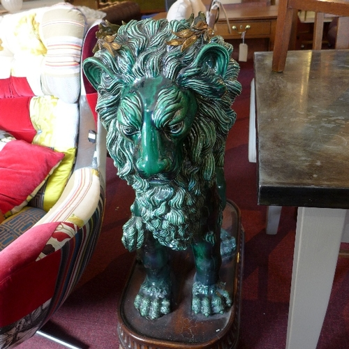 216 - A pair of large green glazed ceramic lions, in seated position, with gilt metal crowns, raised on ma...