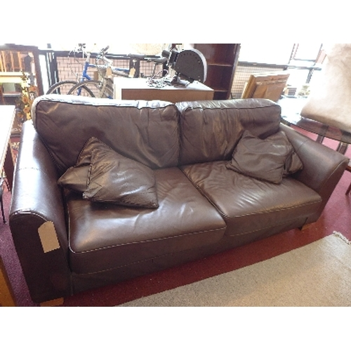362 - A contemporary brown leather three seater sofa, raised on bracket feet...