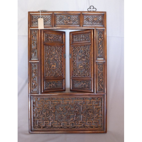 1007 - A large late 19th/early 20th century Chinese hardwood wall plaque, with two hinged doors, having pan...