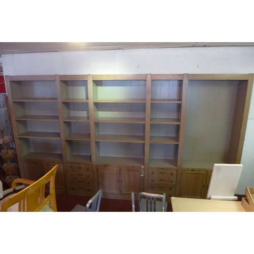 1047 - A Roche Bobois three section bookcase, having adjustable shelves above six cupboard doors and eight ...