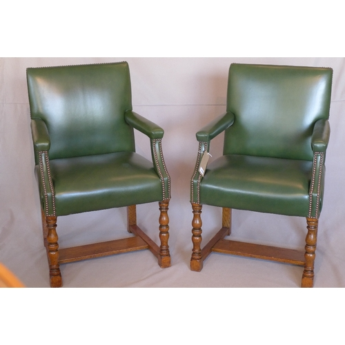 1055 - A pair of Howard & Sons oak Gainsborough chairs, with green leather stud bound upholstery, raised on...