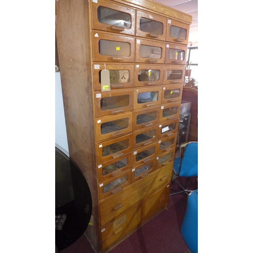 230 - An early to mid 20th century light oak Haberdashery cabinet with 24 glass fronted drawers, above two...