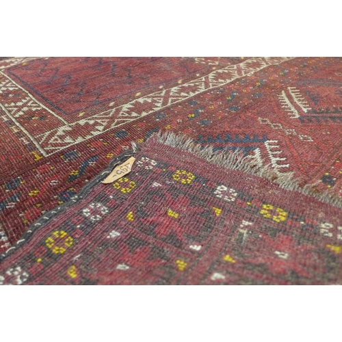 43 - A antique Afghan rug, the temple design ivory rectangular medallion on a terracotta ground within a ...