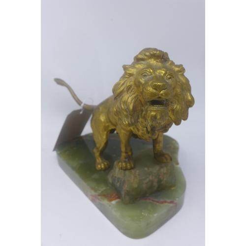 51 - A gilt spelter sculpture of a lion on an onyx base...