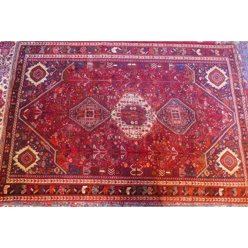 52 - A south west Persian Qashgai carpet, with a triple pole medallion with repeating petal and animal mo...