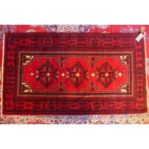 58 - A north east Persian Turkoman rug, 200cm x 113cm, with a triple pole medallion on a rouge field with...