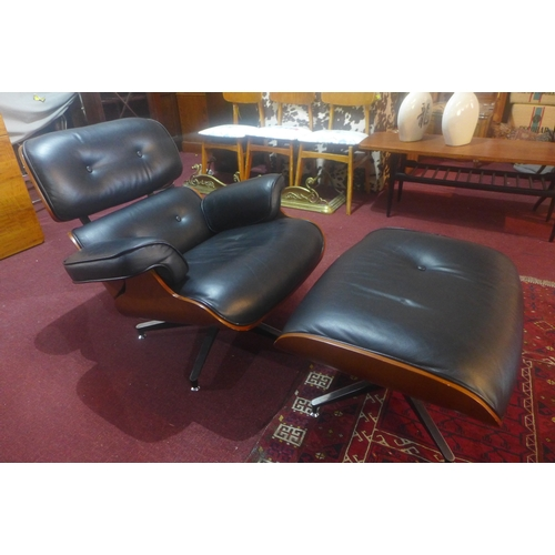 309 - An Eames style black leather lounge chair and ottoman...