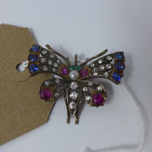 1004 - A Continental Austrian yellow metal brooch in the form of a butterfly inset with rubies, sapphires a...
