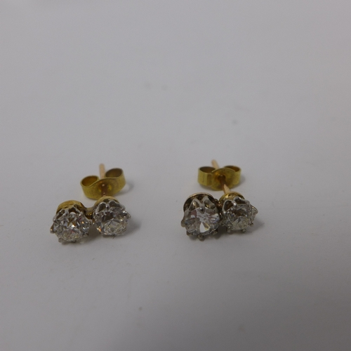 1007 - A pair of ladies yellow metal and diamond stud earrings, each have two round cut diamonds...
