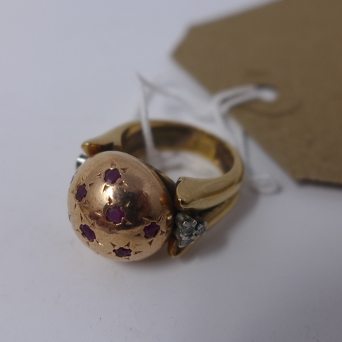 1015 - A ladies yellow metal dress ring in globe form, inset with rubies and diamonds (probably gold)...