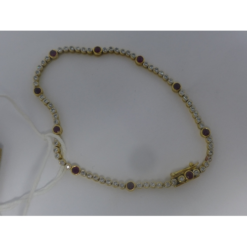1040 - A ladies 18ct yellow gold tennis bracelet inset with diamonds and rubies, with jewellery clasp, mark...