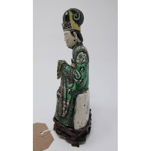 1026 - A late 17th / early 18th century Chinese stoneware seated figure, green glazed, raised on hardwood s...