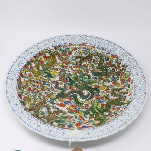 29 - A large Chinese charger, hand painted with dragons amongst stylised clouds within floral border, bea...