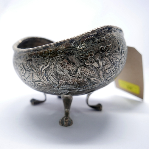 34 - A white metal concave bowl, repousse decorated with griffins amongst flowers, on paw feet...