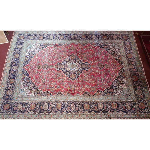 1022 - A Central Persian Kashan carpet, central double pendent medallion with repeating spandrels and petal...
