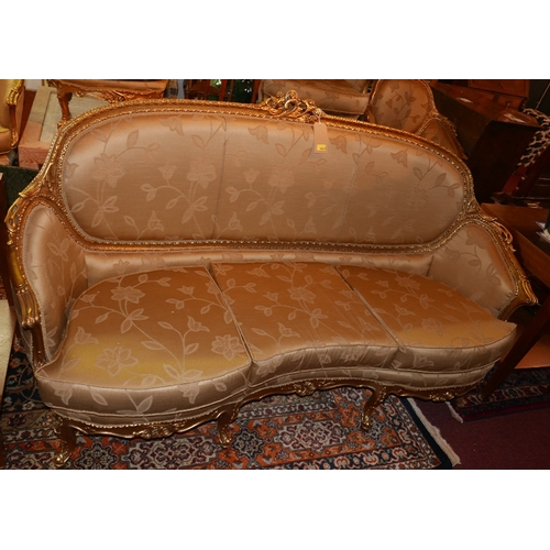 1015 - A Louis XV style giltwood sofa, with golden silk upholstery, raised on cabriole legs...