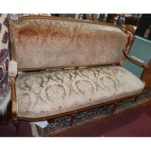 1048 - An early 20th century French walnut sofa, parcel gilt, with floral damask upholstery, raised on reed...