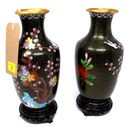 9 - A pair of Chinese cloisonne vases with floral decoration on a black ground, raised on hardwood stand...