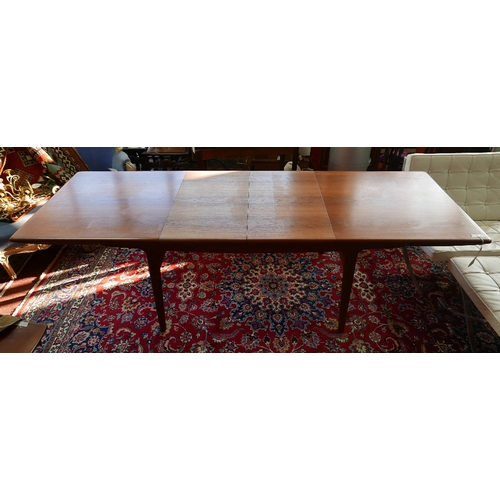 104 - A mid 20th century Danish MK craftsmanship teak dining table, with two extra leaves raised on tapere...