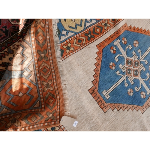 136 - A Caucasian carpet, triple diamond medallions on an ivory field, within geometric borders, fringed, ...
