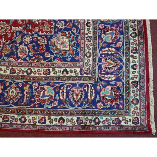 66 - A North East Persian Meshad carpet, signed, central double pendant medallion with repeating petal an...