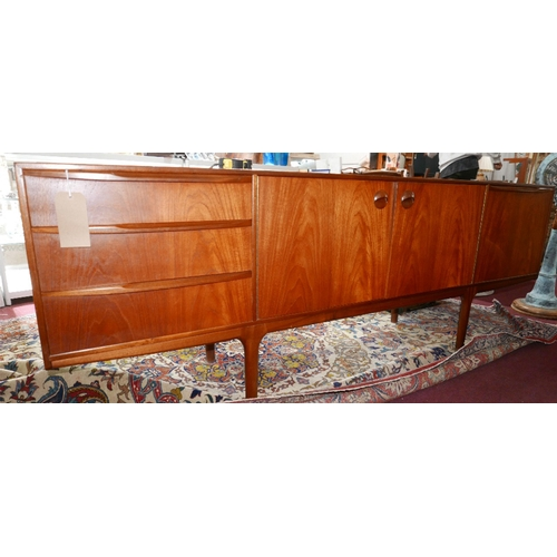 102 - A mid 20th century A.H Mcintosh teak sideboard, with three drawers and three cupboard doors, raised ...