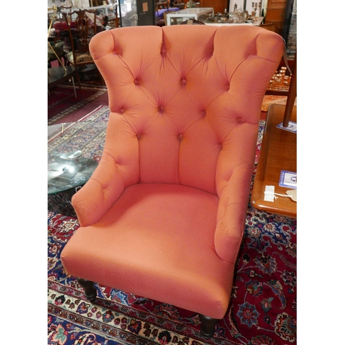 293 - A pair of contemporary wing back armchairs, with orange button back upholstery, raised on turned leg...