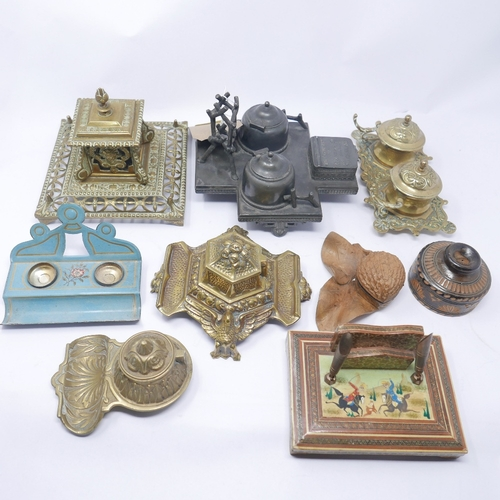 179 - A collection of nine ink stands to include one pewter, four brass, two treen, one toleware and one m...
