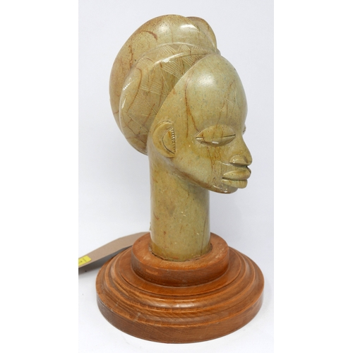 73 - A carved stone bust of an African lady with elaborate coiffure, on stepped circular oak base, H.32cm...