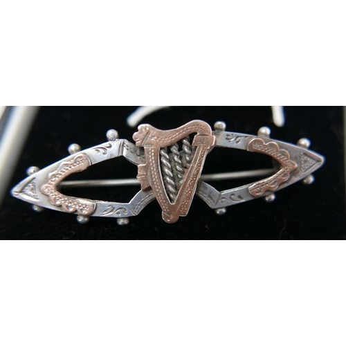 35 - An antique sterling silver and rose gold sweetheart brooch centrally set with a rose gold Celtic har...