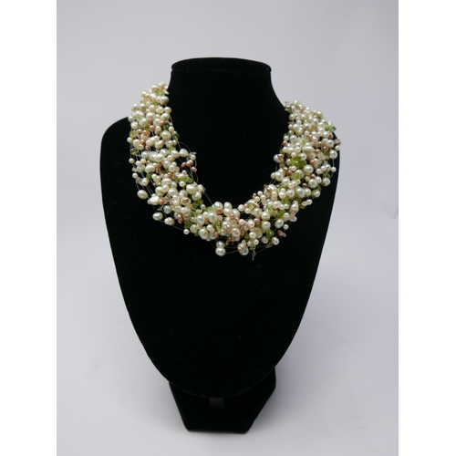 48 - A multi-strand collar necklace composed of white and pink freshwater pearls and peridot beads, with ...