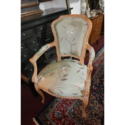 182 - A 20th century French limed beech open armchair, with floral silk upholstery raised on carved cabrio...