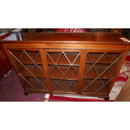 326 - An early 20th Century mahogany triple bookcase with astragal glazed doors enclosing shelves raised o...