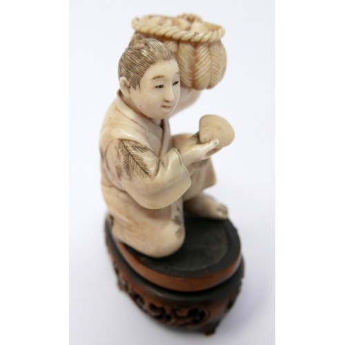 18 - A Meiji period Japanese carved ivory okimono depicting a crouching figure with basket of shells on a...