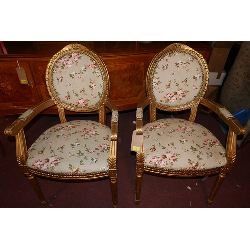 327 - A pair of French Louis XV style carved giltwood fauteuils with floral upholstery over fluted support...
