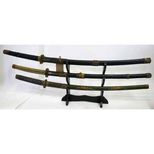 10 - Three early 20th century Japanese samurai swords, to include one with a green lacquered case, signed...