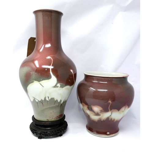 137 - Two early 20th century Japanese vases both hand decorated with white cranes on a mottled plum colour...