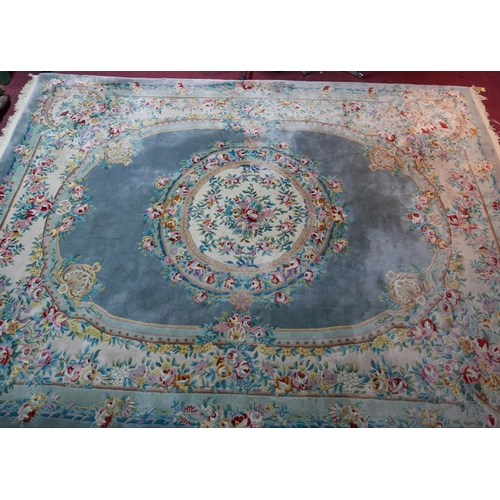 175 - A large 20th century Chinese woollen carpet with central floral medallion on an egg shell blue groun...