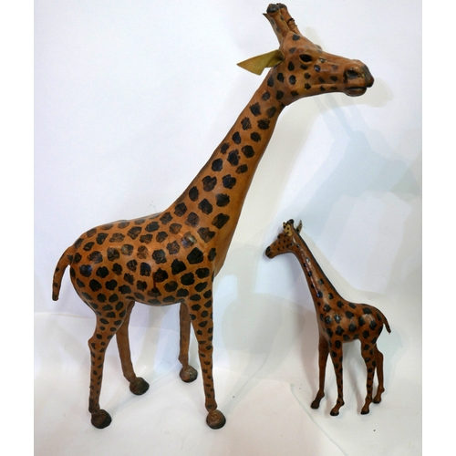 21 - A vintage leather giraffe, H.87cm, together with a vintage leather baby giraffe, H.45cm...