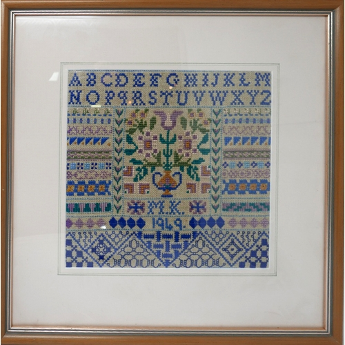 40 - A mid 20th century woollen sampler dated 1949, framed and glazed, in shades of blues, greens and lil...