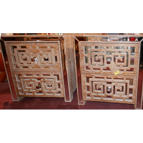 379 - A pair of contemporary limed wooden bedside chests, with bevelled mirrored tops and two fretwork cla...