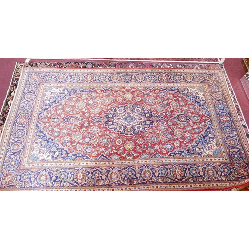 36 - A Central Persian Kashan carpet. Central double pendent medallion with repeating spandrles and petal...