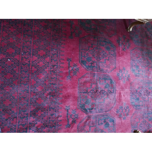 12 - A large antique Russian Afghan bokhara carpet, with gull motifs on a red and black ground, contained...