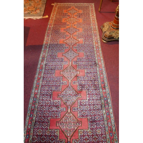 34 - A North West Persian Senngh runner. Repeating diamond shaped medallion with an all over heratie moti...